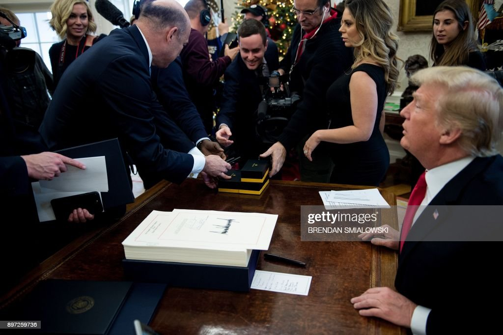 Members of the press reach for pens offered by US President Donald Trump after he signed a tax reform bill in the Oval Office of the White House December 22, 2017 in Washington, DC. / AFP PHOTO / Brendan Smialowski