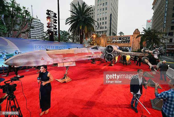 Members of the press report in front of a replica Xwing fighter from the Star Wars movie franchise at the premiere of Walt Disney Pictures and...