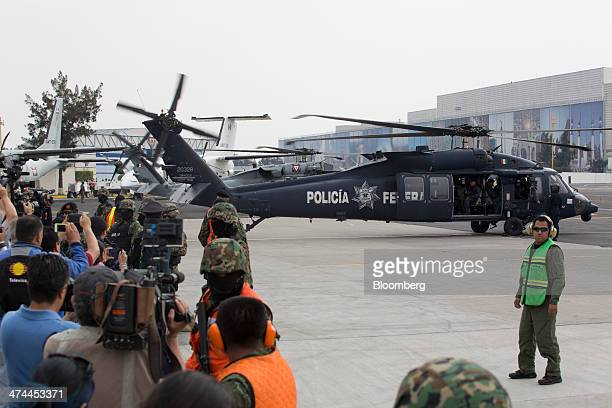 """Members of the press take photographs as drug trafficker Joaquin """"El Chapo"""" Guzman is seated in a Federal Police helicopter with Mexican security..."""