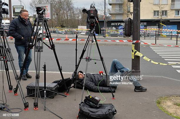 Members of the press work near the Hyper Cache supermarket where people have left floral tributes to the hostages who were killed at the kosher...