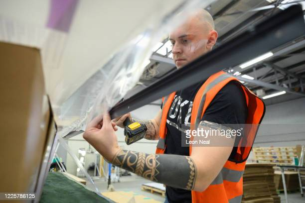 Members of the production team insert the rivets on the frame of a dividing screen for the Morrison's chain of supermarkets at the HL Display factory...