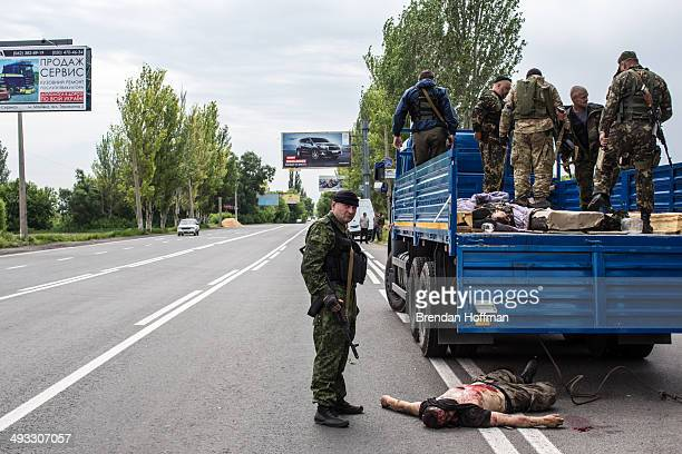 Members of the proRussia Vostok Battalion stand over the body of a proUkrainian militia fighter on May 23 2014 in Pisky Ukraine At least eight people...