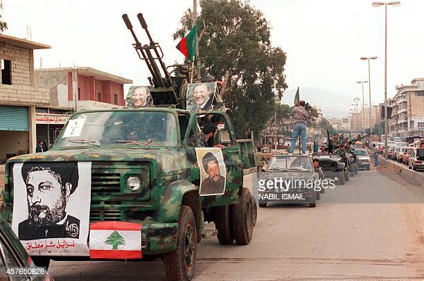 Members of the proSyrian Amal militia the first political organization of Lebanon's Shiite Muslims with posters of their leader Nabih Berri and of...
