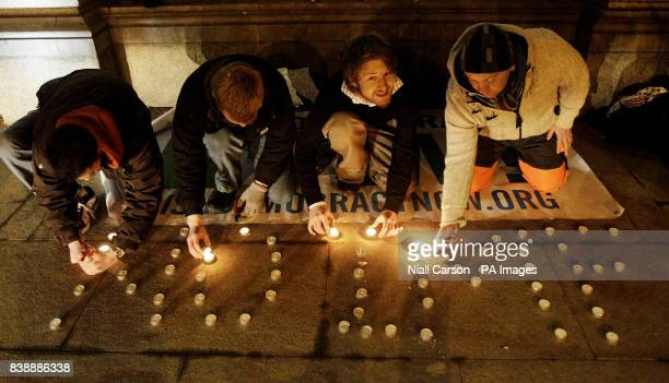 Members of the protest group Irish Democracy Now light candles spelling out NO IMF outside Leinster House Dublin as the Government carries crucial...