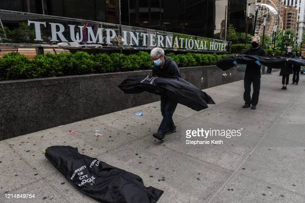 Members of the protest group Rise and Resist place mock body bags in front of the Trump International Hotel on May 24 2020 in New York City Rise and...