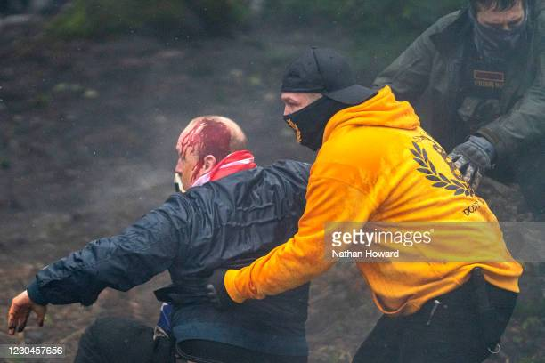 Members of the Proud Boys pull an injured supporter of President Trump to safety during a protest on January 6, 2021 in Salem, Oregon. Trump...