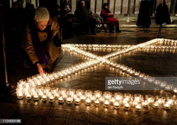 Members of the public add their own candles to the six hundred candles that form the Star of David during an event to commemorate Holocaust Memorial...