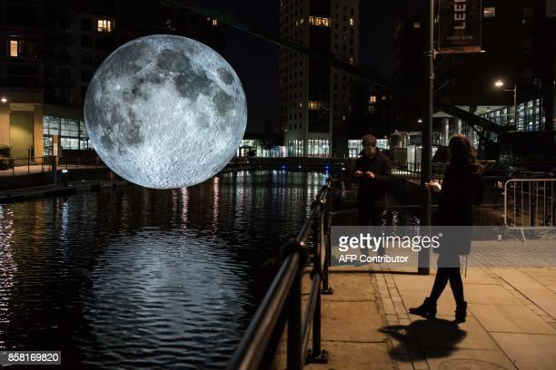 Members of the public admire an illuminated art installation entitled 'Museum of the Moon' which features in the annual 'Light Night Leeds' festival...