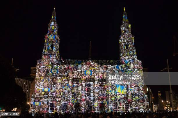 Members of the public admire an illuminated art installation entitled 'Out of the Aire' projected onto Leeds Civic Hall which features in the annual...