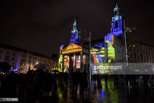 Members of the public admire the artwork 'Telekinetic Rumours' projected onto the Civic Hall and created by Polish artist Pani Pawlosky during the...
