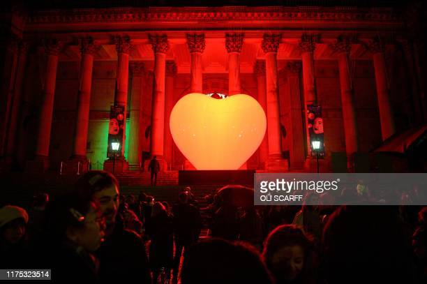 TOPSHOT Members of the public admire the artwork 'With Love' in front of Leeds Town Hall by French artist Franck Pelletier during the annual 'Light...