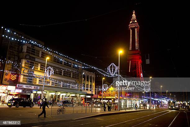 Members of the public admire the Blackpool Illuminations as they walk along the promenade in Blackpool northern England on September 11 2015 The...