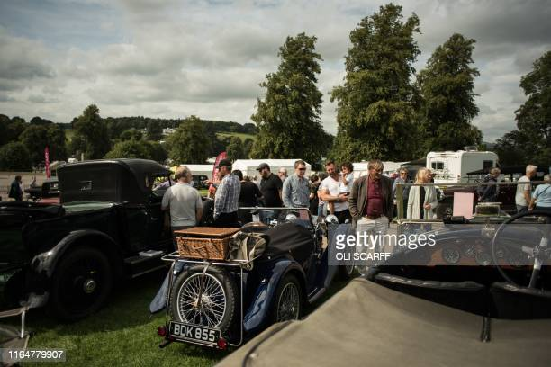 Members of the public admire the classic cars on display on the first day of the Chatsworth Country Fair in the grounds of Chatsworth House, near...