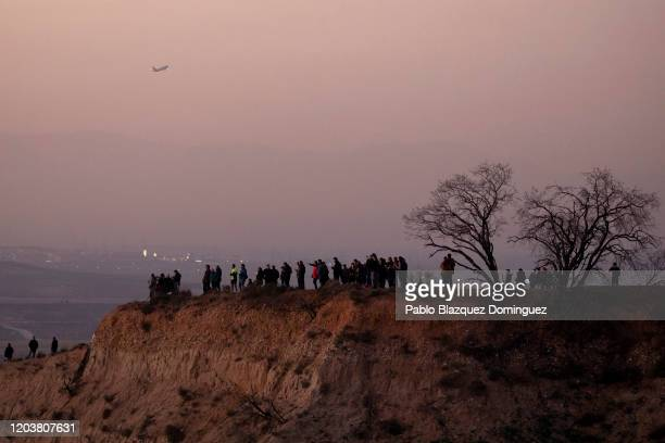 Members of the public and journalists stand on a hill to watch an emergency landing of an Air Canada flight near Adolfo Suarez MadridBarajas Airport...