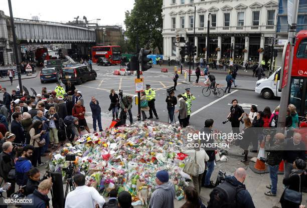 Members of the public and press stand and work around flowers layed south of London Bridge in London on June 7 during a gathering following the June...