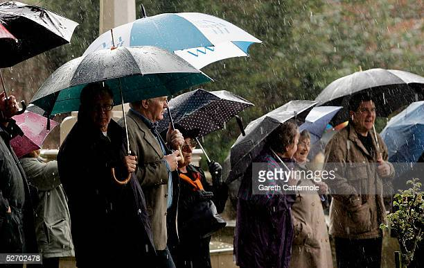 Members of the public are seen in the grounds of The Parish Church of Saint Mary the Virgin during the funeral of actor Sir John Mills takes place...