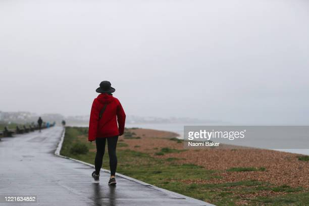 Members of the public are seen walking in the rain at Lee-on-the-Solent beach front on April 28, 2020 in Lee-on-the-Solent, England . British Prime...
