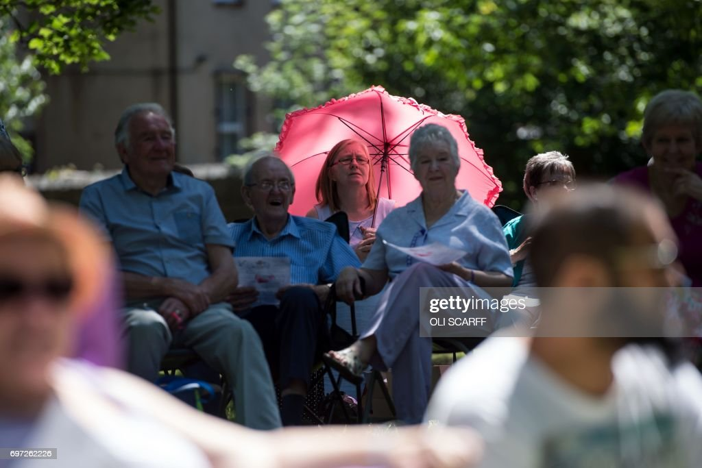 Members of the public attend a 'Great Get Together' community service and picnic in memory of murdered Member of Parliament Jo Cox, marking the first anniversary since her killing, in the grounds of All Saints Church in Batley, northern England on June 18, 2017. The Great Get Together weekend is Inspired by murdered Labour MP Jo Cox's belief that we have more in common than which divides us, a line from her first speech to Parliament, and is a community initiative designed to unite people and communities on the streets and parks of their neighbourhoods. The 41 year-old Labour Party MP, Jo Cox, was assassinated by a pro-Nazi sympathiser in a terror attack in her constituency in northern England on June 16, 2016. /