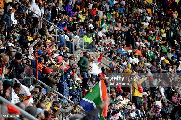 Members of the public attend the Nelson Mandela memorial service at the FNB Stadium on December 10 2013 in Johannesburg South Africa Over 60 heads of...