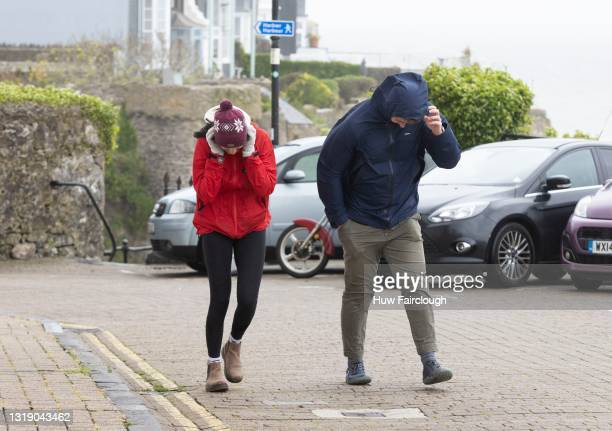 Members of the public battling the wind on The Paragon on May 20, 2021 in Tenby, Wales. The Met Office have issued a Yellow Beware warning with winds...