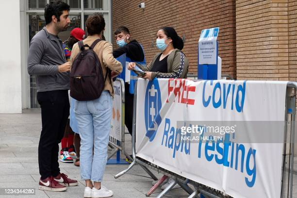 """Members of the public chat outside a """"Free Covid-19 Testing"""" site in south London, on July 31, 2021. - Coronavirus case numbers increased more than..."""