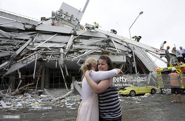Members of the public comfort each other outside the PGG-Wrightson building in central Christchurch after a 6.3 earthquake on February 22, 2011. The...