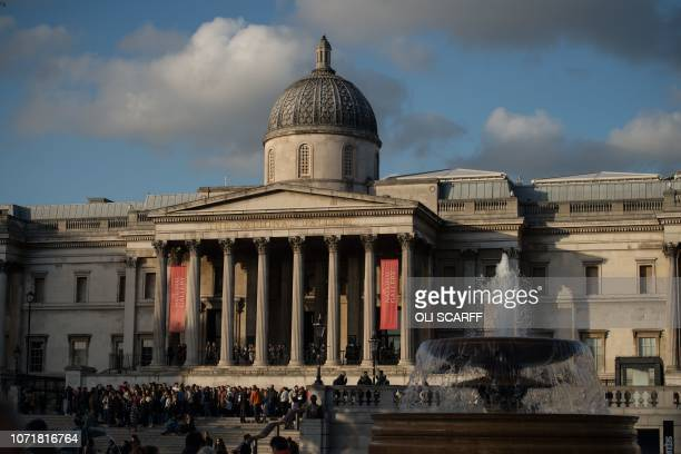 Members of the public congregate outside The National Gallery in Trafalgar Square in the late afternoon sunshine in central London on December 11...
