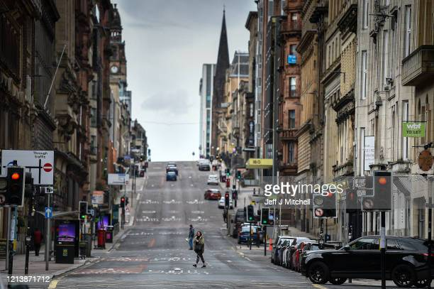 Members of the public cross St Vincent Street on March 21 2020 in Glasgow Scotland Coronavirus has spread to at least 182 countries claiming over...