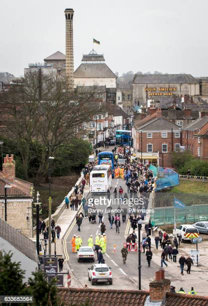 Members of the public cross Tadcaster Bridge as it reopens more than a year after its partial collapse which came to symbolise the destruction of the...