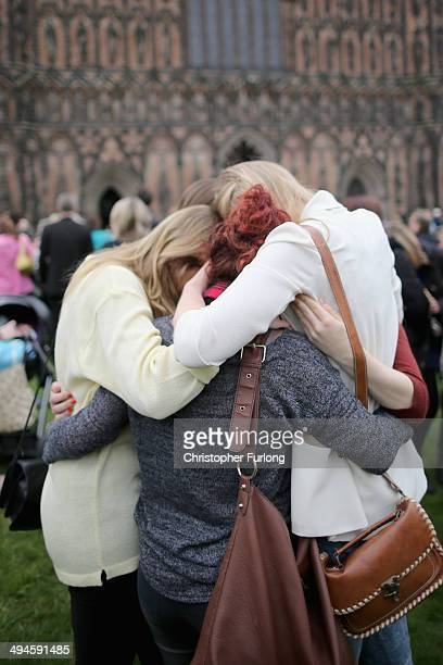 Members of the public embrace as they take part in a minute of celebration for the life of teenage cancer fundraiser Stephen Sutton during a vigil at...