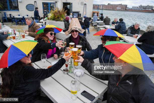 Members of the public enjoy a drink outside at The Still & West pub at Spice Island on April 12, 2021 in Portsmouth, England. England has taken a...