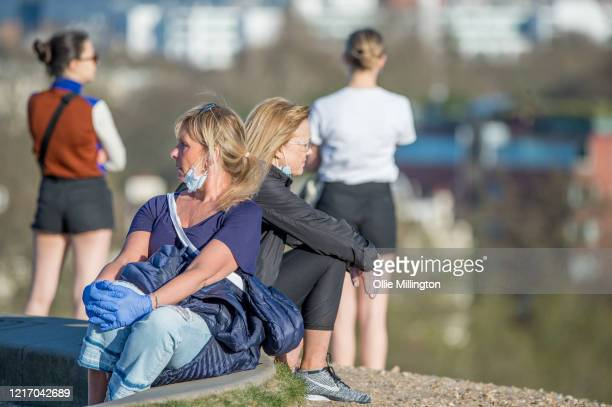 Members of the public enjoy the day's warm weather on Primrose Hill on April 5, 2020 in London, England. The British government announced strict...