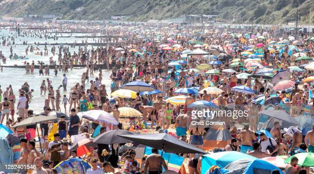 Members of the public enjoy the sunshine on Bournemouth Beach on June 24,2020 in Bournemouth,England.The UK is experiencing a summer heatwave, with...