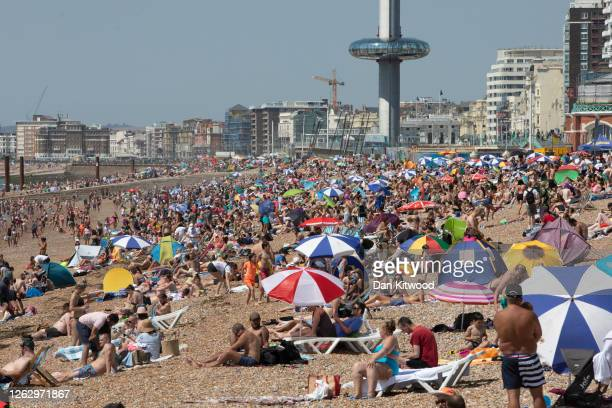 Members of the public enjoy the sunshine on Brighton Beach on July 31 2020 in Brighton England High temperatures are forecast across the UK today...