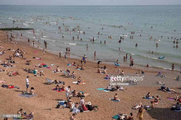 Members of the public enjoy the sunshine on Brighton Beach on July 31, 2020 in Brighton, England. High temperatures are forecast across the UK today,...