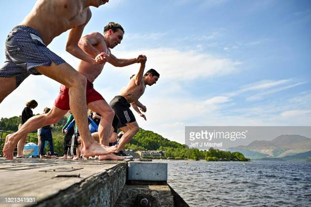 Members of the public enjoy the warm temperatures by jumping off Luss Pier into Loch Lomond on July 2, 2021 in Luss, Scotland. Much of the country is...