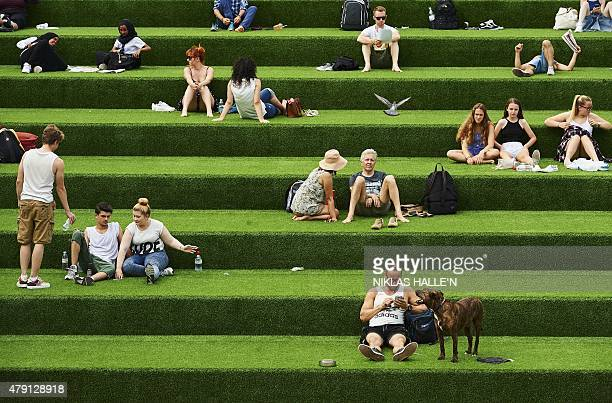 Members of the public enjoy the warm weather in central London on July 1 2015 A blistering heatwave sweeping through Europe on Wednesday brought...