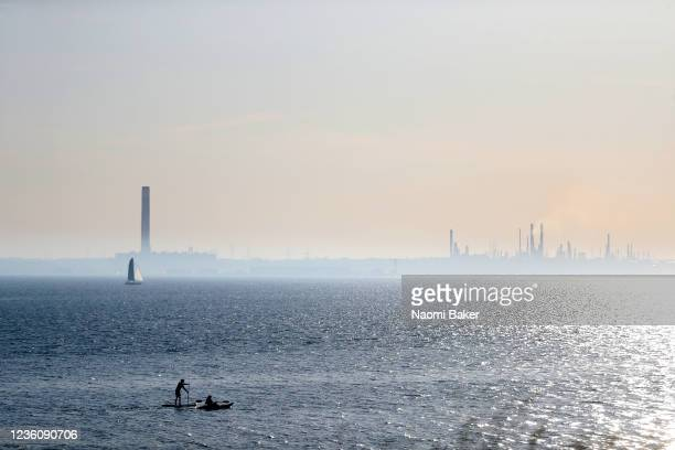 Members of the public enjoy water sports including kayaking and paddle boarding at the beach on a sunny day as Fawley Oil Refinery is seen in the...