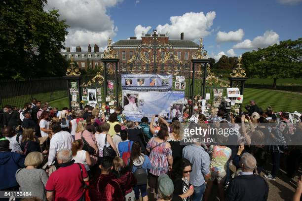 Members of the public gather at the tributes of flowers, candles and photographs outside one of the gates of Kensington Palace in London on August 31...