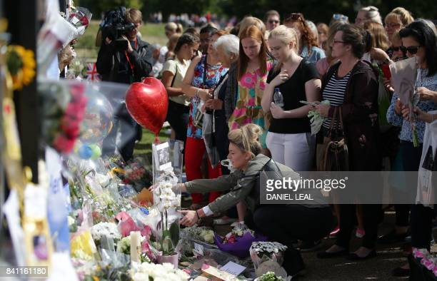 Members of the public gather at the tributes of flowers candles and photographs outside one of the gates of Kensington Palace in London on August 31...