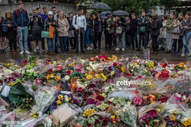 Members of the public gather near flowers on the South side of London Bridge close to Borough Market in London in tribute to the victims of the June...