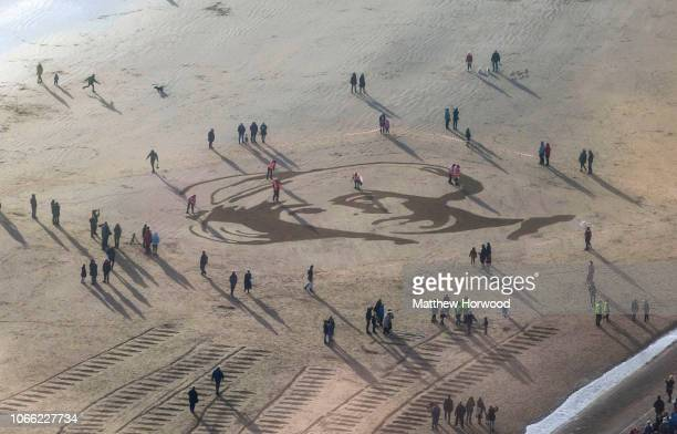 Members of the public gather on Swansea Bay Beach Wales for filmmaker Danny Boyle's Pages of the Sea commissioned by 1418 NOW to mark the centenary...