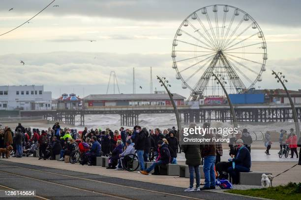 Members of the public gather on the promenade to pay their respects to comedian Bobby Ball as his funeral cortege passes Blackpool Tower and the...