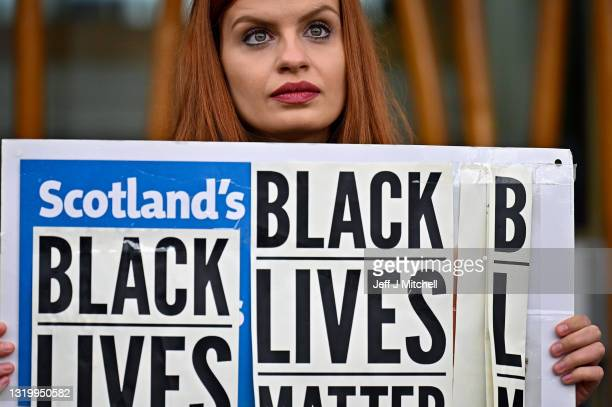 Members of the public gather outside the Scottish Parliament to mark the first anniversary of Georg Floyd's death on May 25, 2021 in Edinburgh,...