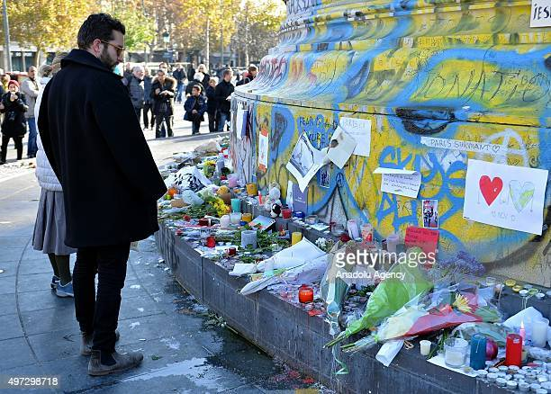Members of the public gather to lay flowers and light candles at La Belle Equipe restaurant on Rue de Charonne following Friday terrorist attacks in...
