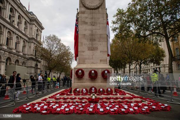 Members of the public gather to look at wreaths left following the National Service of Remembrance at The Cenotaph on November 8, 2020 in London,...