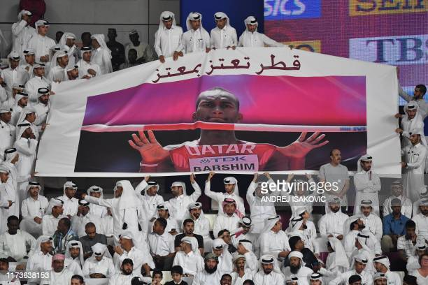 Members of the public hold a banner picturing Qatar's Mutaz Essa Barshim as they attend the Men's High Jump final at the 2019 IAAF Athletics World...