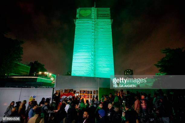 Members of the public hold a vigil and commemoration near Grenfell Tower in west London at midnight June 14 2018 to honour the 71 people who died...