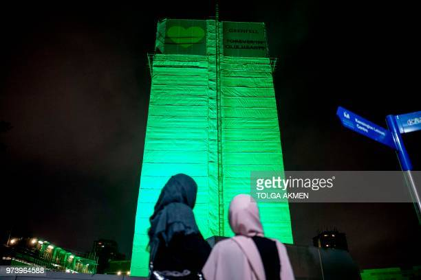 TOPSHOT Members of the public hold a vigil and commemoration near Grenfell Tower in west London at midnight June 14 2018 to honour the 71 people who...