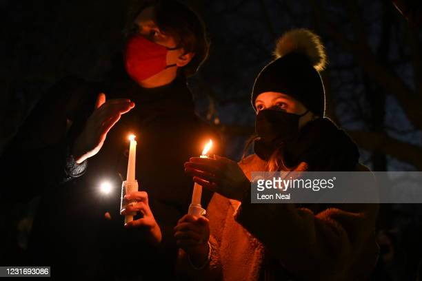 Members of the public hold candles as they gather for a vigil for Sarah Everard at the bandstand on Clapham Common on March 13, 2021 in London,...
